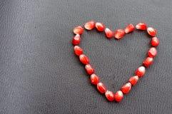 Granatäpplefrö som staplas i formen av en hjärta på en svart bakgrund Royaltyfri Foto