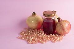 Granatäpplefrukt, granatäpplefrö och granatäpplefruktsaft på en rosa bakgrund Mat- och drinkbegrepp Royaltyfri Fotografi