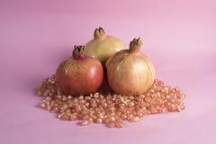 Granatäpplefrukt och granatäpplefrö på en rosa bakgrund Royaltyfri Foto