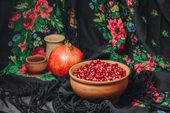 Granatäpplekorn i en keramisk bunke på en tappningtygbakgrund, granatäpplefrukt, keramisk tillbringare, keramisk platta, etnisk s arkivfoton