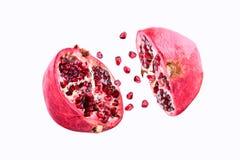 Granatäpplet brast i flykten på en vit bakgrund som isolerades Klipp det halva granatäppleflyget i luften fruktpomegranate som vi Royaltyfri Fotografi
