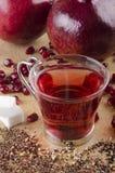 Granatäpplet kärnar ur te med socker i ett exponeringsglas Arkivbilder