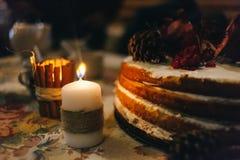 Granatäpplet varvade kakan i ljuset av en tjock vaxstearinljus som sloggs in i en hampakabel royaltyfri bild