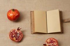 Granat Apple e taccuino che si trovano su una tela di sacco sorge Fotografia Stock Libera da Diritti