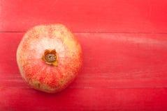 Granatapfel auf einem roten hölzernen Hintergrund stockfotografie