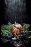 Granatapfel auf einem schwarzen Hintergrundrauchen Lizenzfreie Stockfotos