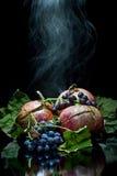 Granatapfel auf einem schwarzen Hintergrundrauchen Stockfotos