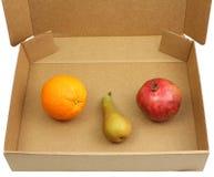 Granatapfel, Birne und Orange in einem Kasten Lizenzfreie Stockbilder