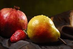 Granatapfel, Erdbeere und Birne auf dem Seidengewebe, besprüht mit Wasser Stockfoto