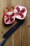 Granatapfel geschnitten zur Hälfte mit scharfem Messer Lizenzfreie Stockfotografie