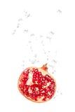 Granatapfel im Wasser mit Luftblasen Stockfotografie