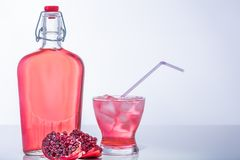 Granatapfel mit Juice Bottle und vollem Glas mit Eis und Stroh lizenzfreie stockfotos