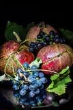 Granatapfel und wilde Trauben auf einem schwarzen Hintergrund Stockfotografie