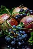 Granatapfel und wilde Trauben auf einem schwarzen Hintergrund Stockfotos