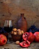 Granatapfel, Walnüsse, Trauben und Wein Stockbild