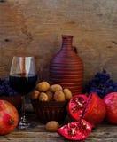 Granatapfel, Walnüsse und Glas Wein Stockfotos