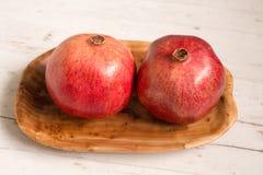 Granatapfelfrucht auf hölzerner Servierplatte stockfoto