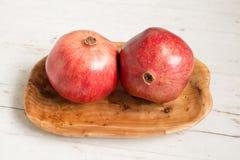 Granatapfelfrucht auf hölzerner Servierplatte stockbild
