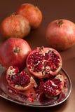 Granatapfelscheiben und -startwerte für Zufallsgenerator auf silbernem Tellersegment Lizenzfreies Stockbild