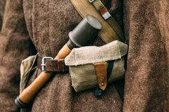 Granate close-up on a Soviet overcoat. Overcoat Soviet soldier with a grenade in his belt during the Second World War. Reconstruction Royalty Free Stock Photo