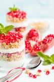 Granatowa parfait - słodki organicznie płatowaty deser z granola płatkami, jogurtem i czerwonymi dojrzałymi owoc ziarnami, zdjęcie stock