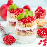 Granatowa parfait - słodki organicznie płatowaty deser z granola płatkami, jogurtem i czerwonymi dojrzałymi owoc ziarnami, zdjęcia royalty free