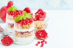 Granatowa parfait - słodki organicznie płatowaty deser z granola płatkami, jogurtem i dojrzałymi owocowymi ziarnami, zdjęcie royalty free