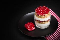 Granatowa parfait - słodki organicznie płatowaty deser z granola płatkami, jogurtem i owoc ziarnami na czarnym tle, zdjęcie royalty free
