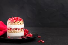 Granatowa parfait - słodki organicznie płatowaty deser z granola płatkami, jogurtem i owoc ziarnami na czarnym tle, obraz stock