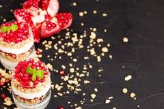 Granatowa parfait - słodki organicznie płatowaty deser z granola płatkami, jogurtem i owoc ziarnami na czarnym tle, zdjęcie stock