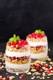 Granatowa parfait - słodki organicznie płatowaty deser z granola płatkami, jogurtem i owoc ziarnami na czarnym tle, zdjęcia royalty free