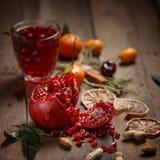 Granatowa sok z granatowami i wysuszonymi owoc na drewnianym stole Kraju styl fotografia royalty free