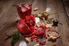 Granatowa sok z granatowami i wysuszonymi owoc na drewnianym stole Kraju styl zdjęcia stock