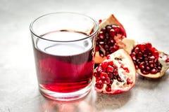 Granatowa sok z ziarnem na kamienia stołu tle Zdjęcie Stock