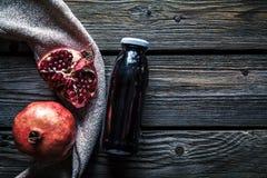 Granatowiec i butelki esencja lub tincture na drewnianym wieśniaka stole fotografia royalty free