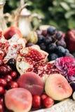 Granatowiec i winogrona w talerzu na drewnianym stole zdjęcia stock