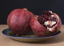 Granatowiec owoc z dojrzałymi ziarnami na rocznika talerzu, Zdjęcia Stock