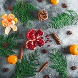 Granatsfrucht, Mandarine Zimt, Anis und Winterbaumaste auf dunklem Hintergrund Weihnachtsniederlassung und -glocken Flache Lage B Stockfotos