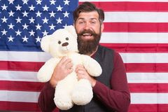 A grand all glory flag. Happy hipster holding teddy bear on american flag background. Bearded man smiling with soft toy. And national flag of united states. If stock images