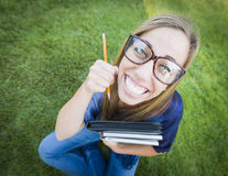 Grand-angulaire humoristique du joli ado avec les livres et le crayon Image stock