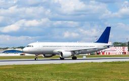 Grand avion blanc d'avion de passagers sur la piste à l'aéroport par jour ensoleillé Photo stock