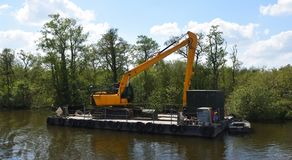 Grand bêcheur mécanique sur le ponton flottant images libres de droits