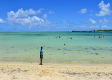 Idyllic tropical sea in sunny day. Grand Baie, Mauritius - Jan 7, 2017. A man walking on the beach in Grand Baie, Mauritius. Mauritius is a major tourist stock photography