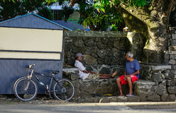 Old men sitting on road in Le Morne, Mauritius Stock Photo