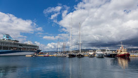 Grand bateau de croisière et plus petits bateaux dans le port Palamos en Espagne, TU Photographie stock libre de droits