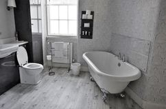Grand Bathroom with old tub. Toilet and wooden flooring. This is as seen in Edinburg, Scotland in UK stock photography