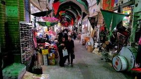 In Grand Bazaar of Kashan, Iran. Kashan, Iran - October 22, 2017: Busy alleyway of old Grand Bazaar, decorated with flags of Muharram Festival, locals walk along stock video