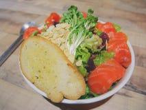 Grand bol de salade de saumons fumés avec le grand morceau de pain à l'ail sur le dessus photos libres de droits