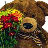 Grand bon ours avec un bouquet des fleurs Image stock