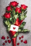 Grand bouquet de roses rouges avec la boucle et carte de voeux avec le coeur, vue supérieure Symbole d'amour Photo libre de droits